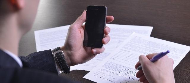 スマートフォンを見ている人の写真